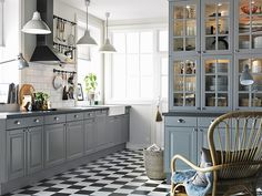 Grey cabinetry, black and white floors, and crisp white trim.