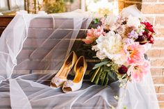 the bridal bouquet of loose, abstract bridal bouquet of white peony, white majolik spray rose, lavender astrantia, burgundy ranunculus, light pink parrot tulip, lavender stock, burgundy dahlia, purple heather, quicksand rose, seeded eucalyptus, ivy & olive leaf with the bridal veil and shoes.
