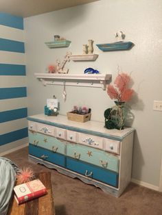 I sanded down the dresser which used to be a dark oak color all over and gave it a beach themed feel. I made the handles by braiding raffia.