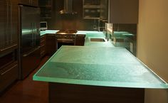 I love the glass counter tops.  I also love how with the touch of a button you can alter the color scheme by way of LED lights mounted underneath.  Perfect for entertaining!!