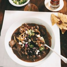"""This richly flavored chili pays homage to the Texas """"bowl of red,"""" in which meat is the star. Mole paste, ancho chile powder, and cumin add depth of flavor. Set out bowls of beans, cheese, onions, and other garnishes so that guests can have their chili just the way they like it."""