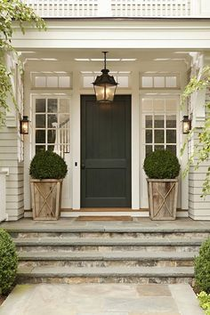 French Country front door, planters, boxwoods and stone steps.