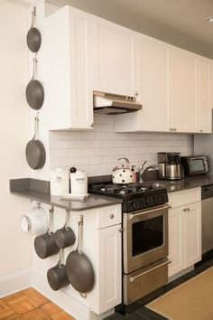 Hang pots and pans - $5 for Command hooks - Instead of taking up valuable cabinet space with these clunky items, use Command Hooks to hang them on an unused wall. See more home hacks at HouseBeautiful.com.