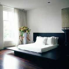 Black platform double bed, a grey satin bedspread and glossy wooden floor | PHOTO GALLERY | Housetohome