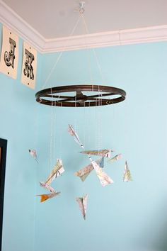 Paper airplane mobile from maps and a wheel rim. Great for a boy's room!