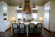 Copper in the Kitchen: Copper range chimney hood with a copper sink and white cabinets