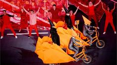 The Pet Shop Boys rode into the Olympic Stadium on rickshaws flanked by cyclists. All are wearing fluorescent orange sculptural headgear designed by the avant-garde British fashion designer Gareth Pugh.
