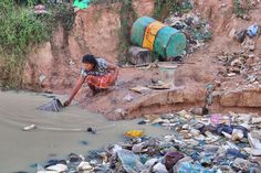 Woman fetches water at a Cambodian rubbish dump