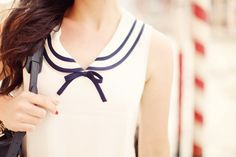 White dress contrasted with a navy striped peter pan collar and bow are very nautical inspired