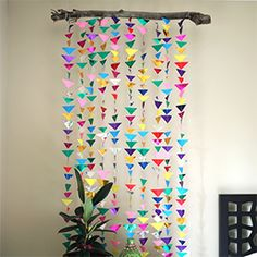 Create a modern and colorful backdrop for a party or children's room using origami paper and a tree branch.
