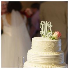 A custom monogram cake topper from Inscribed makes a statement on the simple and elegant cake.