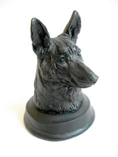 """B8772 £32 or offer INC POST. A handcast sculptured slate desk weight in the form of the head of an Alsatian or German Shepherd dog standing approximately 4.75"""" high to the tip of the dog's ears on a felt covered round integral base. The weight is apparently made out of 500m year old slate by Celtic Castings. (We have no reason to doubt the veracity of the claim). Structurally sound. Weighs almost 470g."""