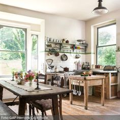 Vintage-Möbel aus unterschiedlichen Holzarten und mediterrane Wandfliesen: Die Küche erinnert an Sommerurlaube in Spanien oder Südfrankreich. Praktisch sind Wandboards mit Haken, an denen man von Kochlöffel bis zur Pfanne, alles aufhängen kann.