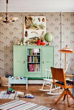 chambre bebe garcon avec grand meuble de rangement et un mur avec papier peint aux motifs fleurs et fruits