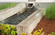 Effective stormwater management in a dense urban area. Swales and stormwater planters collect stormwater from roof downspouts, parking lot ...