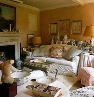 A pair of large and comfortable sofas takes up much of the space in the intimate sitting room the walls of which are a brownish-pink colour chosen by John Fowler