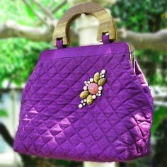 Bright coloured quilted bag, with hand block painted cotton lining with an elegant wooden handle.