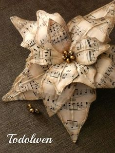 Todolwen - I don't know if there are directions for making this but you get the idea....make poinsetta leaves out of music sheets, use silver colored beads for the centers