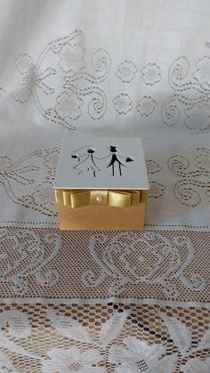 Caixa para lembrancinhas de casamento com recorte de noivinhos na tampa, decorada com laço chanel e fita de cetim. Base na cor dourada e tampa na cor branco. As cores são opcionais, a critério do cliente e combinando com as cores da decoração do casamento.    Opção para colocar trufas, bombons, t...