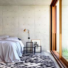 Minimalist bedroom with concrete walls, a simple sconce and large windows