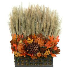 Featuring wheat, lotus pods, quinces, moss, and other natural fall foliage, this centerpiece brings the seasons hues to your table.