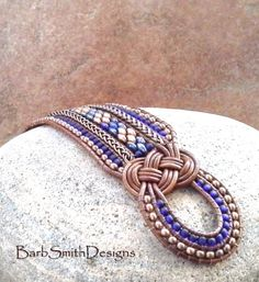 The One in Knots and Chains 5-Row Cuff in Copper n Cobalt  This girl may be all knotted up in the front, but shes happily surrounded in chains! This show-stopper was designed with (2) two beautiful Josephine Knots, a diamond-pattern center row in Matte Copper and Picasso Blue beads surrounded by rows of Antique Copper Wheat Chain, Copper Metal and Cobalt Blue seed beads. It is hand-stitched on Light Brown Indian Leather cord and closes with a double beaded loop and a 5/8 Antique Copper B...