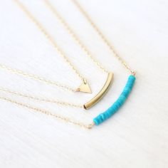 1. 14K gold filled triangle 2. 14K gold filled tube 3. Heishi Turquoise Bar This is a listing for three necklaces. Each has their own clasp. NOTE: please let me know what 3 lengths you would like for the necklaces. Choose between 14-20 + Measurements: Triangle measure : 7mm Tube measures: 1 inch Turquoise length : Approx 2 inches Chain on mannequin is 14, 16 inches and 18 inches  +Materials 14K gold filled triangle 14K gold filled tube Turquoise all metal is 14K gold filled closed with a…