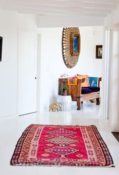 boho interior. colorful patterned rug in an all white interior. via Hippie Hippie Chic