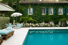 A beautiful country manor pool and garden in northern Italy. Blue shutters, Virginia Creeper ivy clad house, variegated hedge, curtained loggia, white roses, and turquoise cushions