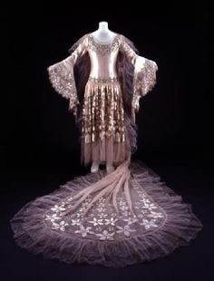 1928, The design, with its cutwork silk and embroidery borders, is a playful, modern variation on the traditional wedding dress. It is said to have been inspired by Renaissance paintings. Hartnell made several wedding dresses of this design
