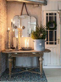 Stunning winter decor with a live tree in a galvanized bucket, candles and rustic candle sticks. The mirror is the perfect finishing touch.