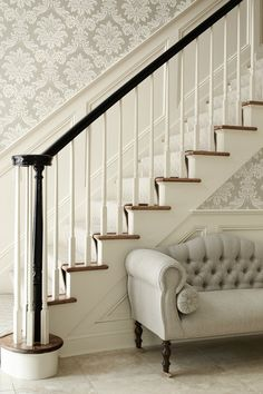 Elegant foyer with silver gray damask wallpaper, wainscoted staircase, glossy black banister and gray tufted settee with caster legs.