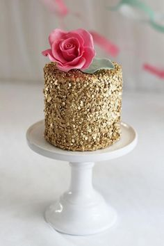 Gold wedding cake with pink flower | Sequin Wedding Cakes with metallic gold and silver accents via @BelleMagazine