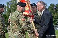 Outgoing U.S. Army Garrison Rheinland-Pfalz commander Col. G. Shawn Wells Jr. watches as incoming commander Col.Keith Igyarto takes the colors from Installation Management Command Europe regional director Michael Formica at the garrison's change-of-command ceremony in Kaiserslautern, Germany, Wednesday, July 6, 2016. At left is Command Sgt. Maj. Edward James Williams III. (Michael Abrams/Stars and Stripes)