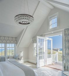 Breathtaking open, light, bright beach house master bed in shades of white spread out thru the angles and  architecture with just the slightest bit of light blue and whitewash, and what looks like a swinging double French door.