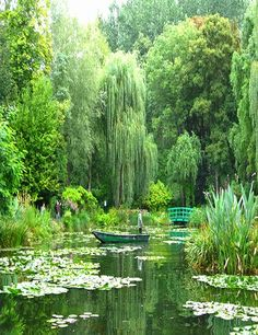 Giverny - on the borders of Normandy - walled water garden planted by Claude Monet consists of white and purple wisterias, water lilies, weeping willows, bamboo, and the green Japanese bridge