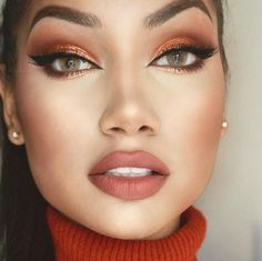 Green eyed beauty with neutral lip, cat liner, face highlighting and pumpkin brown tones on her eyelids.