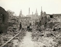 Picking up the pieces: German civilians pick up the pieces of their bombed-out town. General Palmer wrote: 'Well liberated town' on this photo