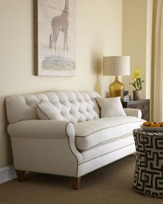 Admirable white tufted sofa with beige shade table lamp and beige wall painting.