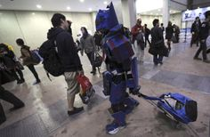 """A costume player, or cosplayer, with cardboard-made robot costume walks around with his belonging during AnimeJapan 2014 anime festival in Tokyo, Saturday, March 22, 2014. Cosplay, or """"costume play,"""" is a growing art form in which fans create detailed costumes to accurately represent their favorite characters in pop culture."""