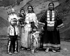 """Julia Goings, wife of Franc C. Goings, a Sioux interpreter for the performers in """"The Red Man"""", poses with her children in front of a painted backdrop of Yellowstone Falls, in the dirt arena at the Empress Hall, at the Golden West and American Industries Exhibition, in Earl's Court, London, England. An unidentified Indian woman stands beside Julia who is holding the hand Leta Goings. The young boy is William Goings. Photo: 1909."""