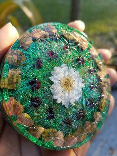 """This listing is for one Daisy- Flower of Life Orgone       Dimensions: 3""""  x  3/4"""" deep    This is a circular shaped piece with the flower of life (sacred geometry) on the front. The vibrant crystals that make up this piece are Unakite and garnet with a layer of crushed clear quartz underneath. All of the crystals in this piece have been cleared, charged and programmed with loving uplifting intentions before being set. The metal in this piece consists of aluminum shavings.       Below are…"""