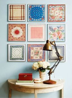 framed collection of handkerchiefs above side table and lamp
