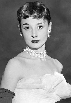 1952?, Audrey Hepburn wearing a tiered ball gown of white net graduated in tones of pale gray to black at the March of Dimes Fashion Show at the Waldorf Astoria Hotel in New York City. Image by Bettman/CORBIS.