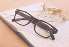 Eyeglasses and book. Arts & Entertainment Photos