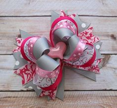 """This listing is for a simply sweet hair bow. The bow is layered in multiple shades of pink, grey and printed ribbon. The bow is finished with a sweet heart pink resin centerpiece. This bow measures about 5"""" and can be mounted on an alligator clip or a french barrette. All ribbon ends are heat sea..."""