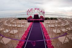 Oceanside fuchsia and purple wedding ceremony coordinated and designed by www.ArielYve.com.  Photography by Michael and Anna Costa Photographers.