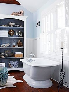 Quintessential Cottage Beaded-board wainscoting, light blue walls, and white wooden shutters create the quintessential cottage bathroom. To take advantage of this bathroom's generous floor space and height, a standard bookshelf Wainscoting Height, Dining Room Wainscoting, Wainscoting Nursery, Wainscoting Stairs, Wainscoting Ideas, Style Nautique, Cottage Bath, Bathroom Inspiration, Bathroom Ideas