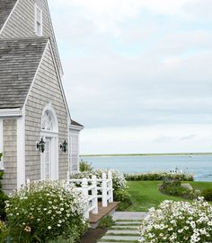 Beach house in Massachusetts. Weathered to silver gray color, the cedar shake siding and bright white trim and millwork are typical of Cape Cod style houses. Close proximity to the ocean somewhat limits the choice of plants that can grow well year-round.