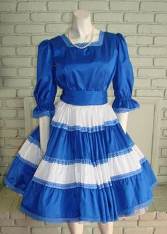 """Vintage 80s  Square Dance Dress Co. Pretty blue with lighter blue lace trim on neck, skirt and hem. Short puffy sleeves, natural waist with a very full skirt.  Long back nylon zipper. Measurements Bust              36"""" Waist            27"""" Hips               Free Length           35 1/2"""" Sweep           244"""""""